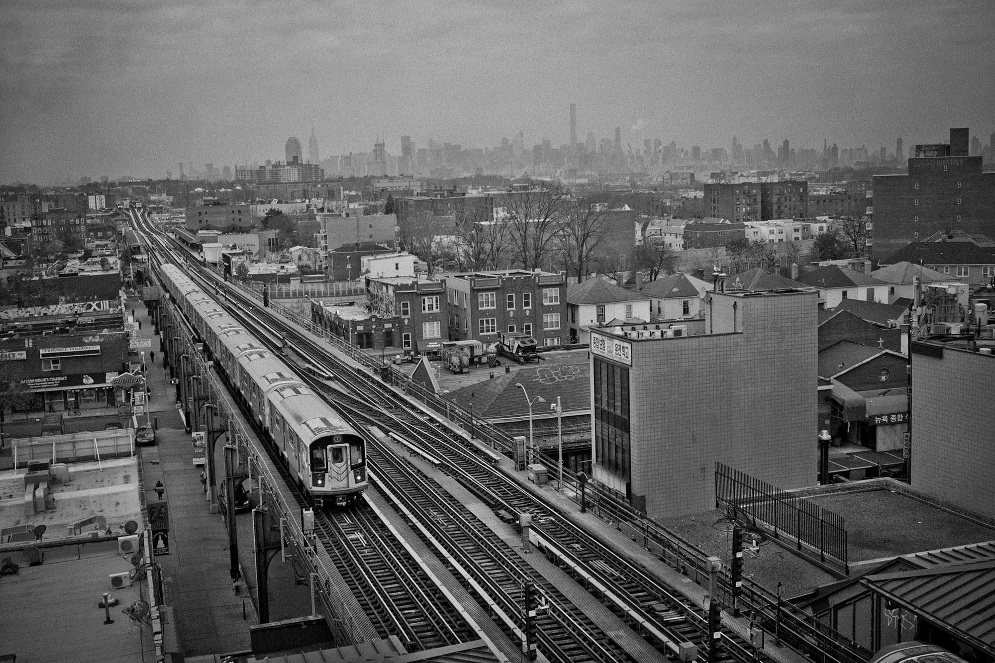 <p>The 74th Street 7 train stop in Jackson Heights, Queens, N.Y., with the Manhattan skyline in the distance in December 2015. (Photo: Yunghi Kim/Contact Press Images) </p>