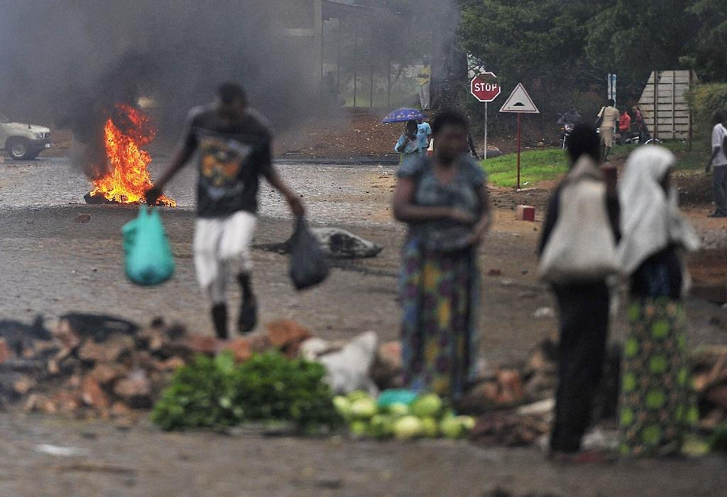 A woman sells her goods near a barricade erected by protesters in Musaga on the outskirts of Bujumbura, on April 30, 2015 (AFP Photo/Simon Maina)