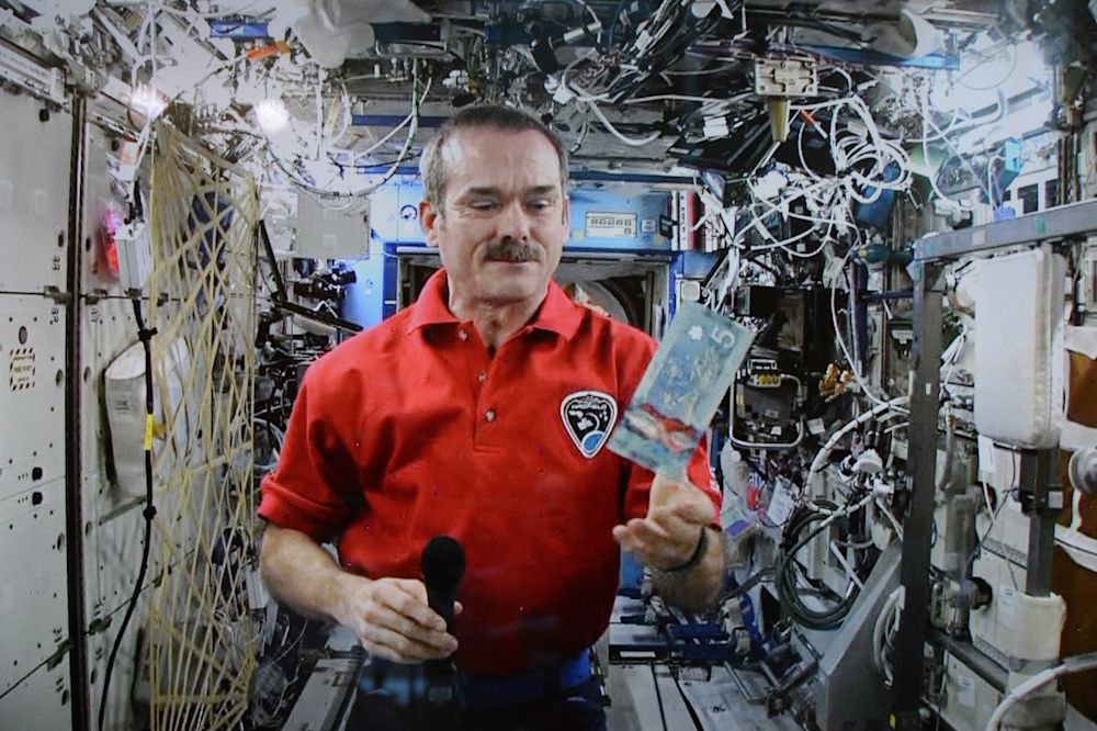 Astronaut Chris Hadfield poses for a photo with a new polymer $5 bank note on Tuesday, April 30, 2013 (CP)