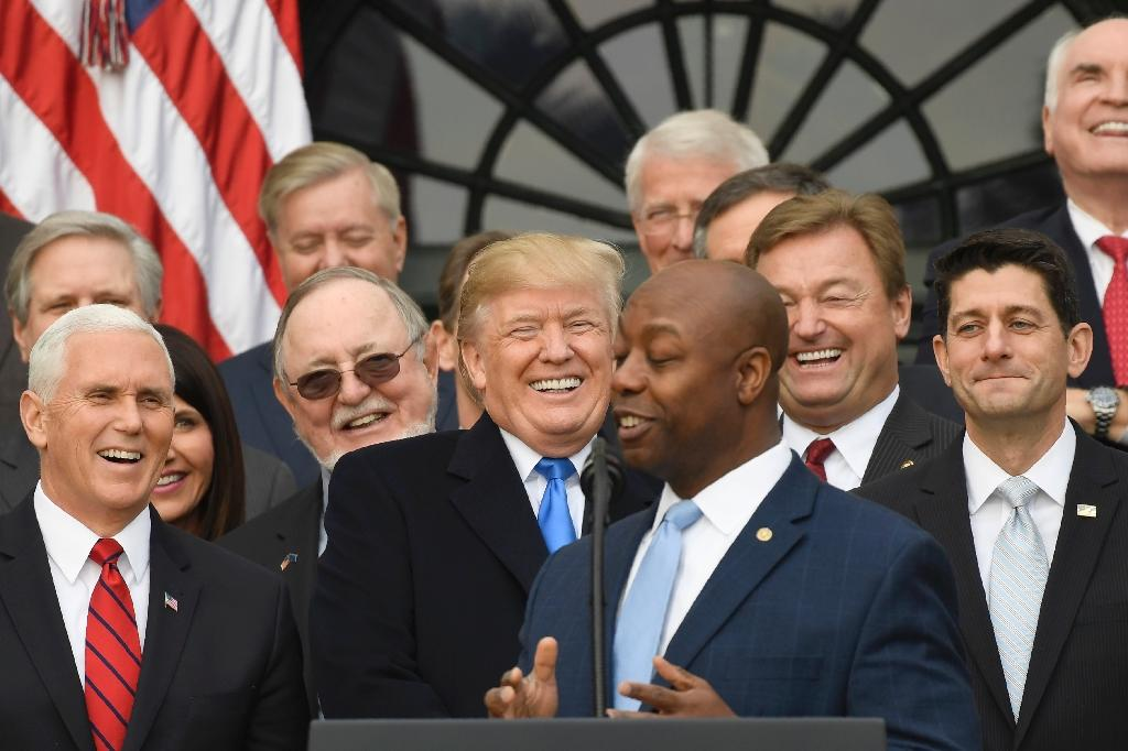 Donald Trump joked, smiled and pumped the hands of Republican lawmakers -- like Tim Scott, here in the foreground -- who returned the favor by singing the president's praises (AFP Photo/SAUL LOEB)