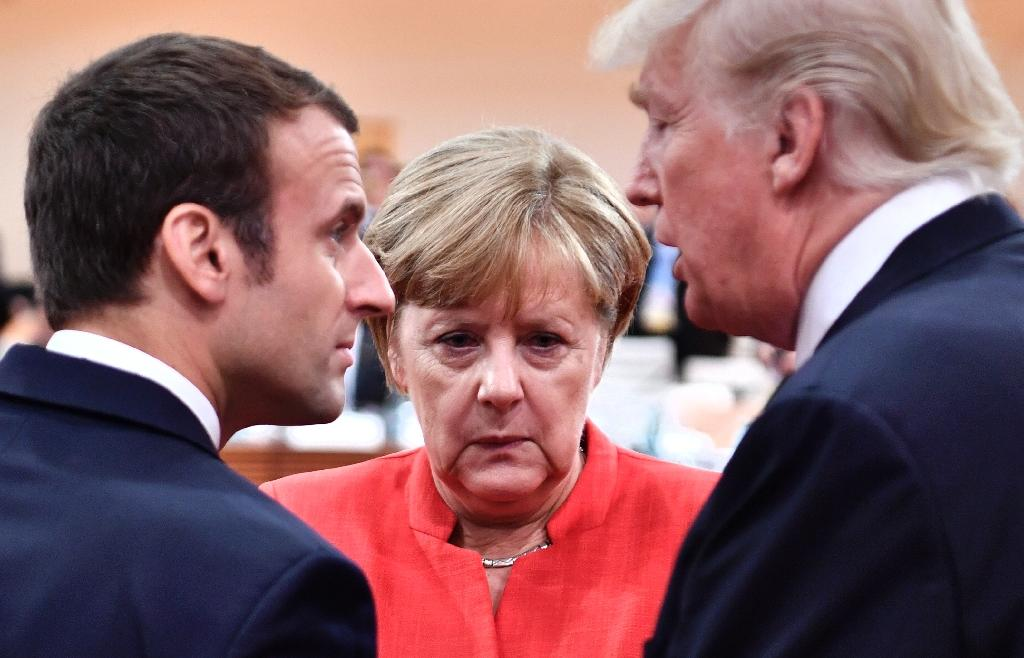 (L-R) French President Emmanuel Macron, German Chancellor Angela Merkel and US President Donald Trump confer at the start of the first working session of the G20 meeting in Hamburg, northern Germany, in July 2017