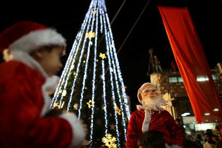 FILE PHOTO: Boys wearing Santa Claus costumes are carried during a Christmas tree lighting ceremony in the northern town of Nazareth, the town of Jesus' boyhood, December 12, 2012. REUTERS/Ammar Awad/File Photo