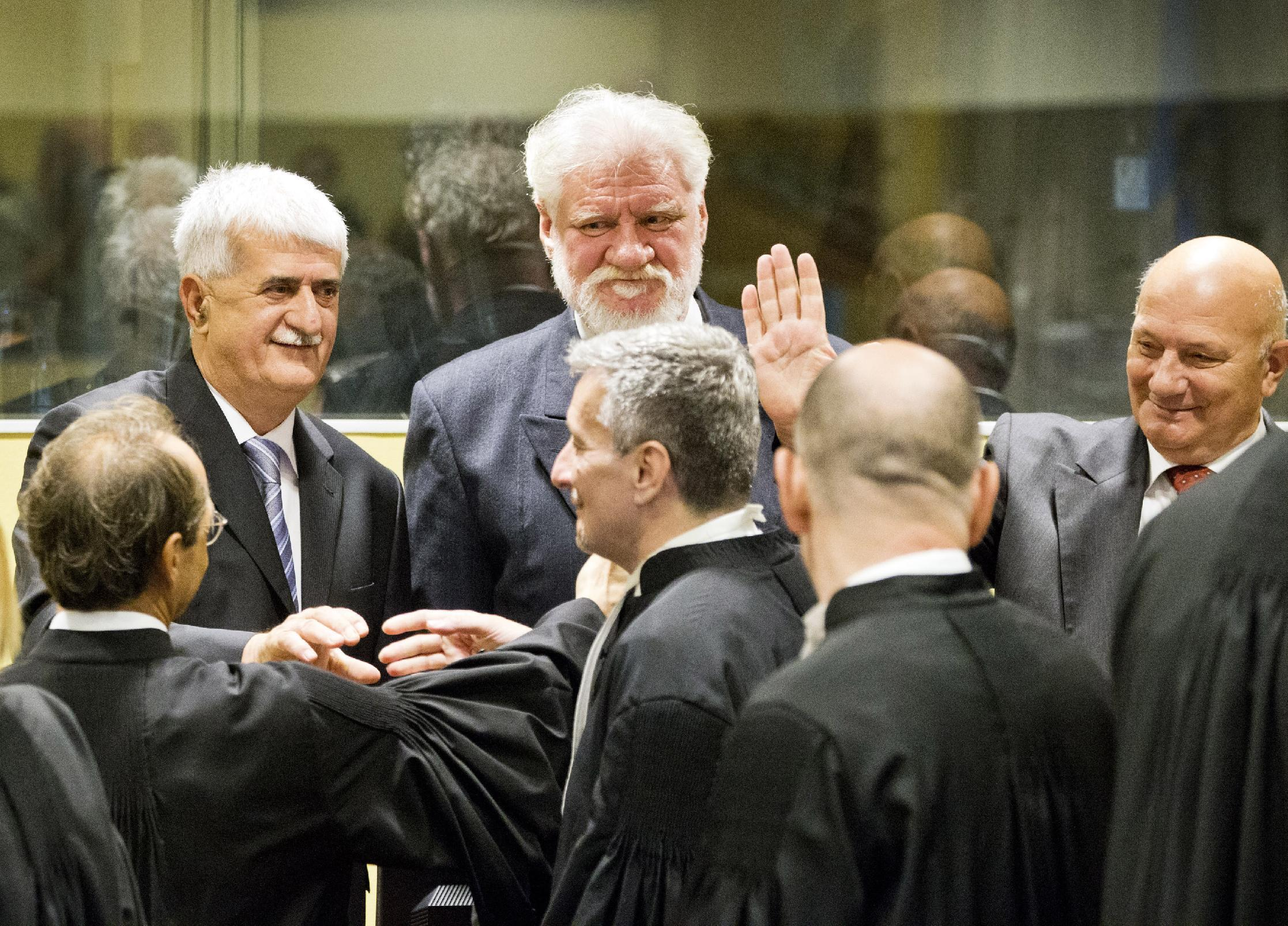 Back row from left, Bosnian Croats Bruno Stojic, Slobodan Praljak and Milivoj Petkovic, greet their lawyers prior to their judgment at the Yugoslav war crimes tribunal (ICTY) in The Hague, Netherlands, Wednesday May 29, 2013. The ICTY is set to deliver verdicts in the long-running trial of six senior Bosnian Croats on charges of crimes against Muslims and Serbs as they tried to carve out a Croat state in Bosnia during the country's 1992-95 war. Prosecutors have asked for sentences of up to 40 years for the suspects. (AP Photo/Jiri Buller, Pool)