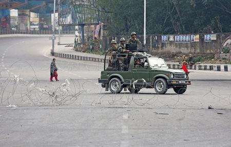 Indian Army soldiers in a vehicle patrol a street as a woman walks past during a curfew in Jammu