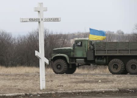 A military vehicle from the Ukrainian armed forces drives past a cross near Artemivsk, eastern Ukraine, March 3, 2015. REUTERS/Gleb Garanich