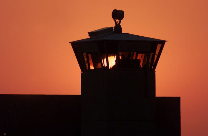 FILE PHOTO: The sun sets behind one of the guard towers at the Federal Penitentiary in Terre Haute