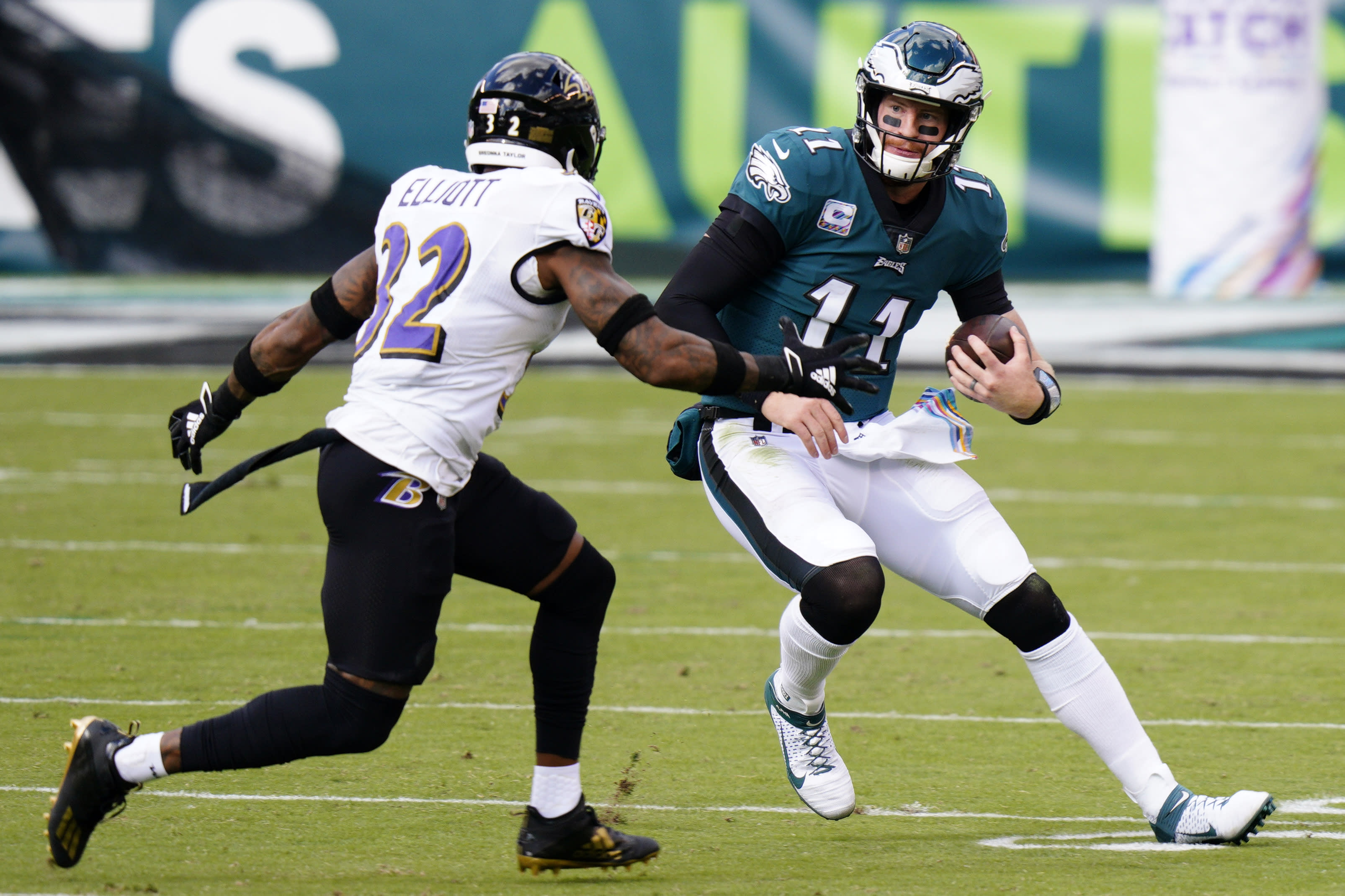 Philadelphia Eagles' Carson Wentz (11) tries to get past Baltimore Ravens' DeShon Elliott (32) during the first half of an NFL football game, Sunday, Oct. 18, 2020, in Philadelphia. (AP Photo/Chris Szagola)