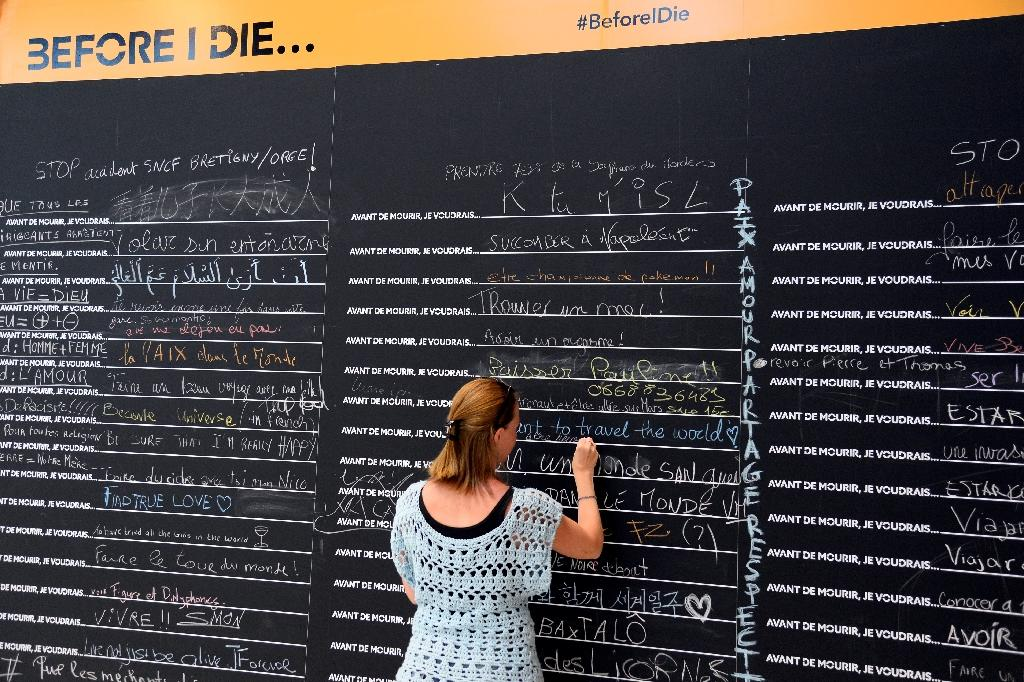 """A person writes a note on the collaborative art installation """"Before I Die"""" by US artist Candy Chang, on August 9, 2016 at the Gare de Lyon in Paris (AFP Photo/Bertrand Guay)"""