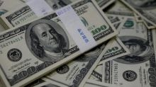 Dollar clings to most of its gains as risk sentiment improves