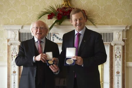 President Michael D. Higgins (L) holds the holds the Seal of Taoiseach as Irish Prime Minister Enda Kenny holds the Seal of Government to office, in Dublin, Ireland May 6, 2016. REUTERS/Clodagh Kilcoyne
