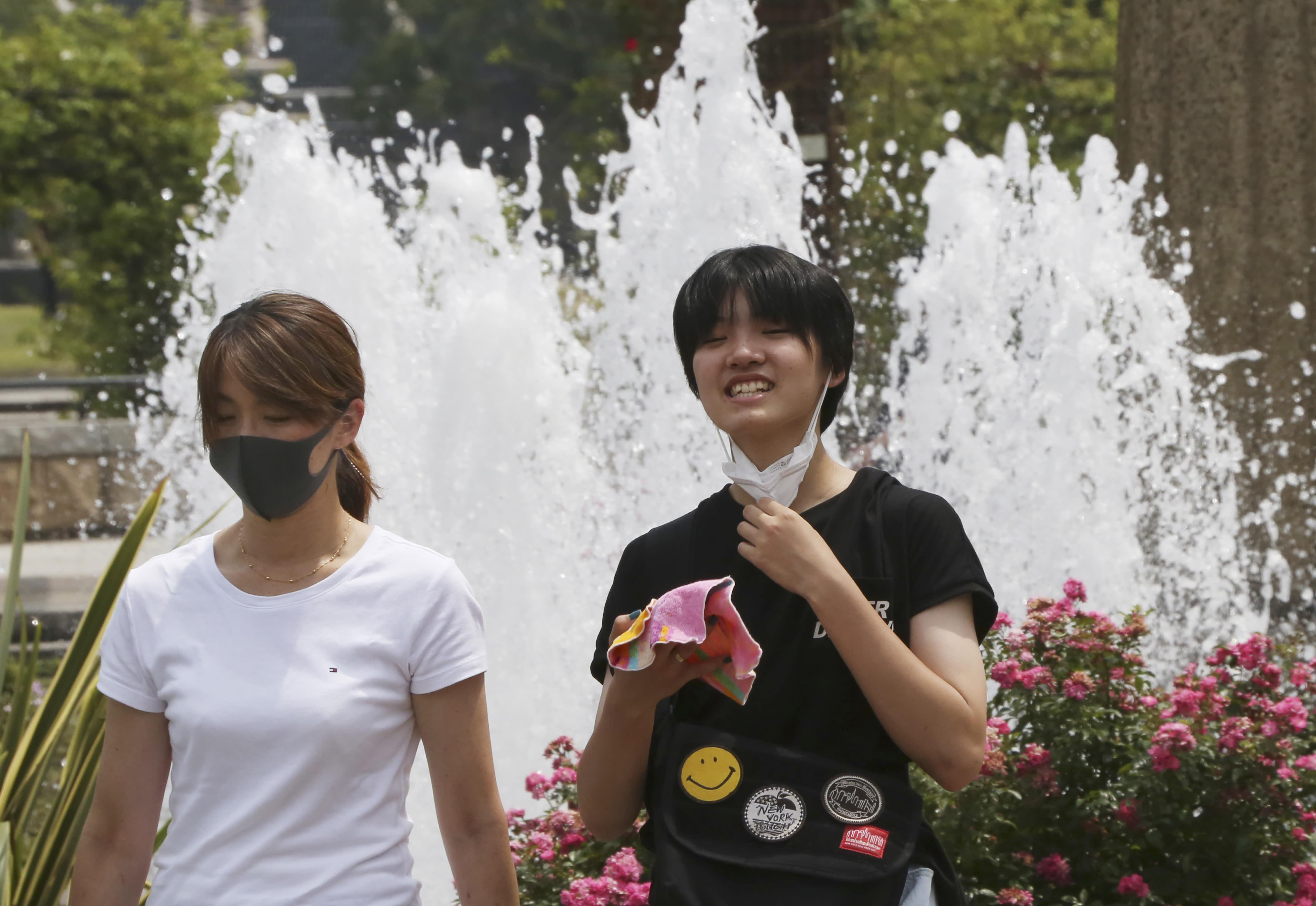 People wearing face masks to protect against the spread of the new coronavirus walk at park in Yokohama near Tokyo, Monday, Aug, 10, 2020. (AP Photo/Koji Sasahara)
