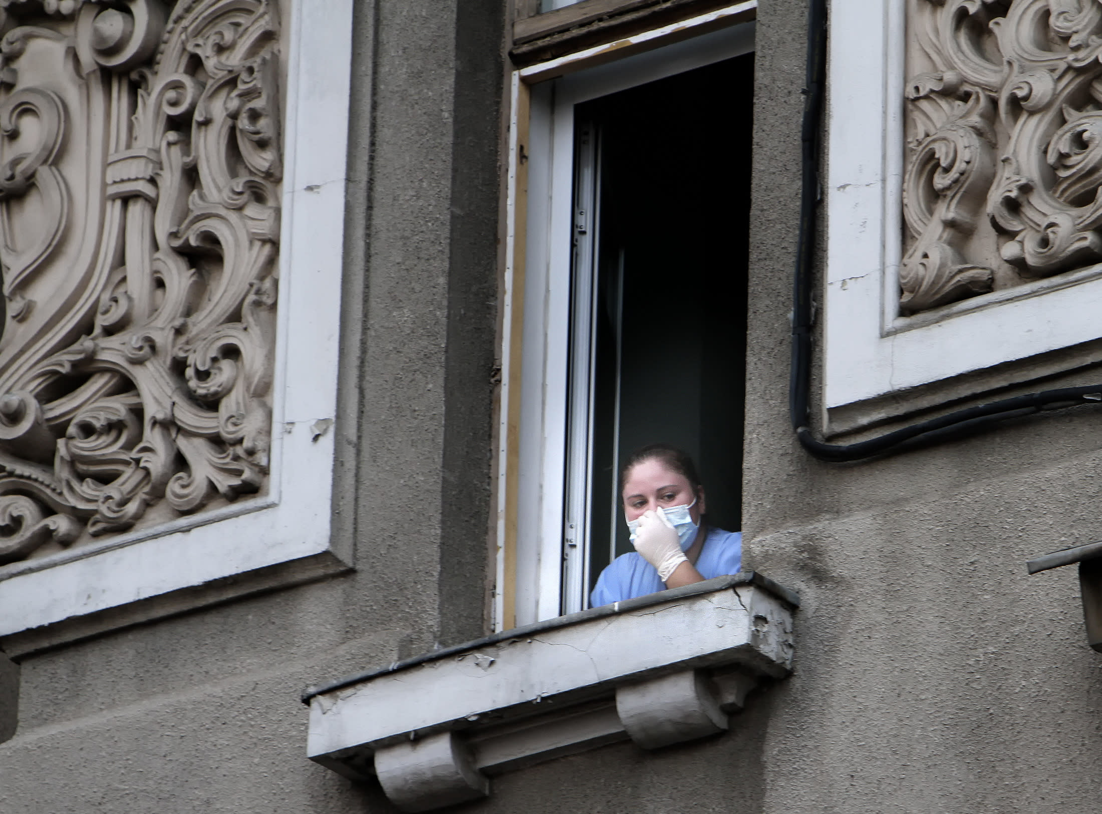 In this Aug. 16, 2010 file photo a nurse looks on from a window of the Giulesti hospital following a fire that left 5 newborn babies dead. Romanian health authorities on Friday, Nov. 30, 2018, temporarily closed the maternity hospital in the capital after over a dozen babies born there recently were diagnosed with a drug-resistant superbug. The Health Ministry said the hospital would stop admissions after the newborns were recently diagnosed with antibiotic-resistant Staphylococcus aureus. (AP Photo/Vadim Ghirda, File)