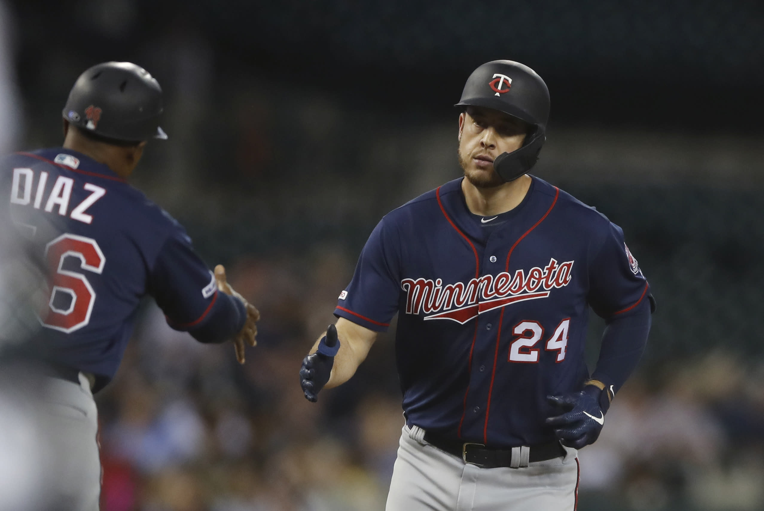 Minnesota Twins' C.J. Cron is greeted by third base coach Tony Diaz after a solo home run during the sixth inning of a baseball game against the Detroit Tigers, Saturday, Aug. 31, 2019, in Detroit. (AP Photo/Carlos Osorio)