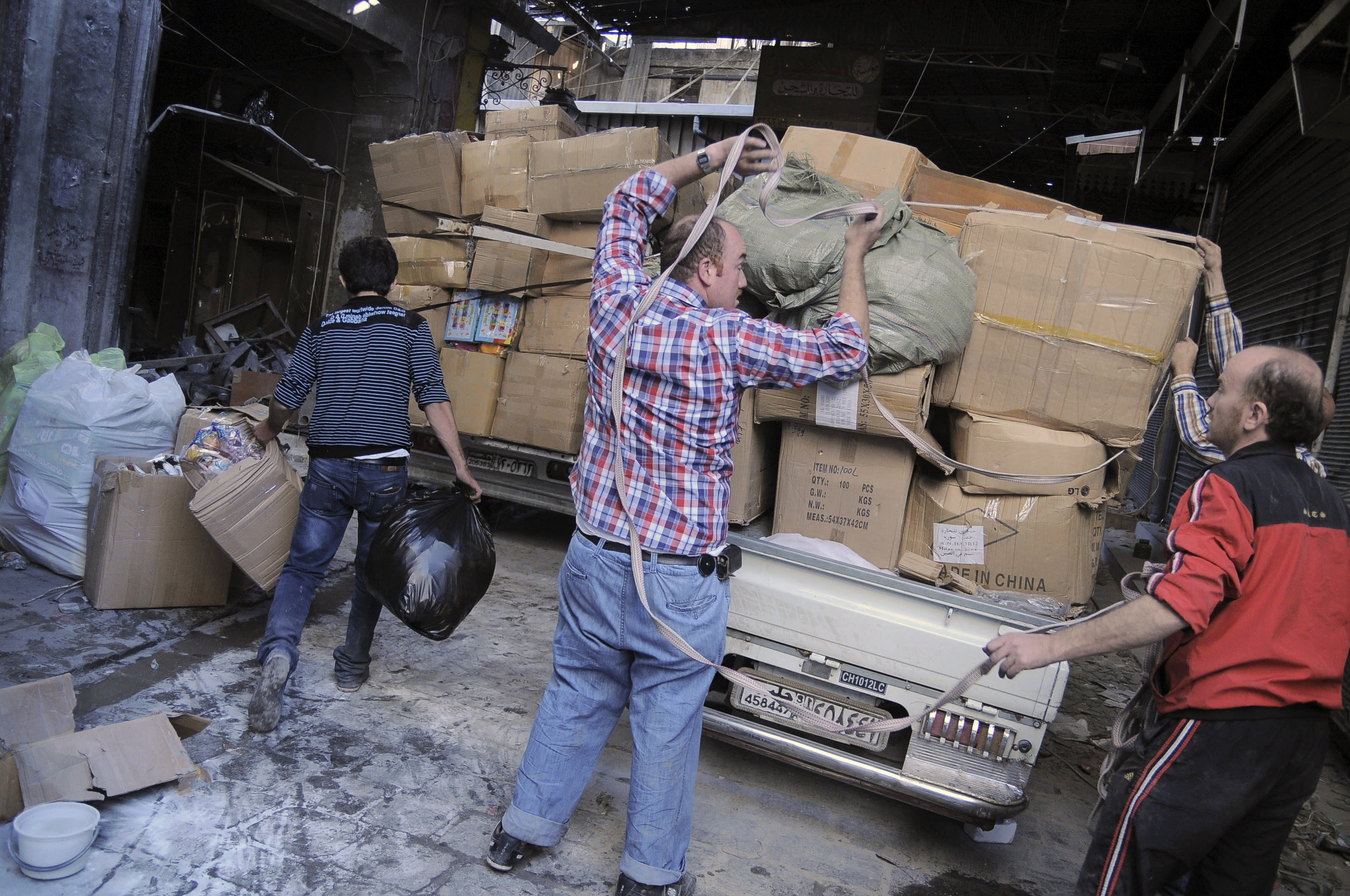 FILE - In this Nov. 6, 2012 file photo, merchants remove their wares from the souk in the Old City of Aleppo, Syria. A year after the opposition fighters stormed Aleppo, taking control of several districts in the city of three million and capturing much of its surrounding towns and villages, the industrial zones that constituted 60 percent of Syrian pre-war economy, are mostly deserted. Some have been looted and several have been burnt down. (AP Photo/Monica Prieto, File)