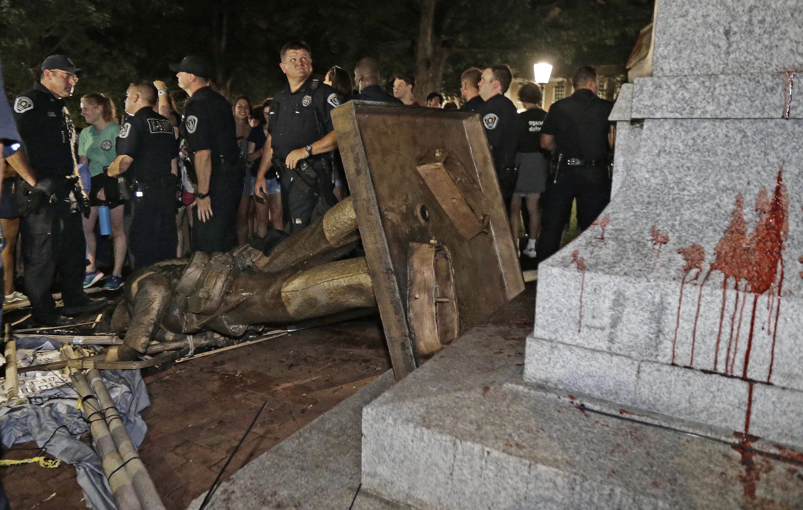 FILE- In this Monday, Aug. 20, 2018 file photo, police stand guard after the confederate statue known as Silent Sam was toppled by protesters on campus at the University of North Carolina in Chapel Hill, N.C. Police are filing charges against three people who they say helped bring down the Confederate statue at North Carolina's flagship university. University of North Carolina Police issued a statement Friday, Aug. 24, 2018, that the department has filed warrants for three people on charges of misdemeanor rioting and defacing a public monument. (AP Photo/Gerry Broome, File)