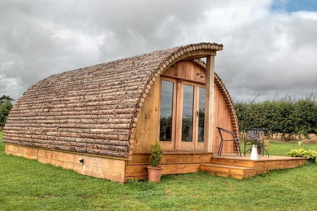 """These new glamping pods in the Isle of Wight offer cosy accommodation for up to six people. The <a href=""""http://tomsecolodge.com/modulogs/"""" target=""""_blank"""">Modulogs</a> pods are fully-insulated and kitted out with heaters, comfy sofas which fold out into sofa beds, log burners, dining tables, compact kitchens with all the essentials, two bedrooms, and a separate shower room and toilet. The pods offer WiFi and each has its own decked area with seating, a BBQ area and a log-burning hot tub. From £300 for two nights."""