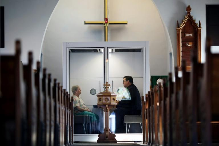 "Pastor Rev. Joel Crouse (R) of Saint John Lutheran Church chats with a parishioner in a see-through, 4' x 6' enclosed compartment, called the ""God Pod"" on September 16, 2020 in Ottawa, Canada"