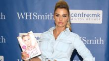 Katie Price flashes mysterious plaster on her stomach at book signing
