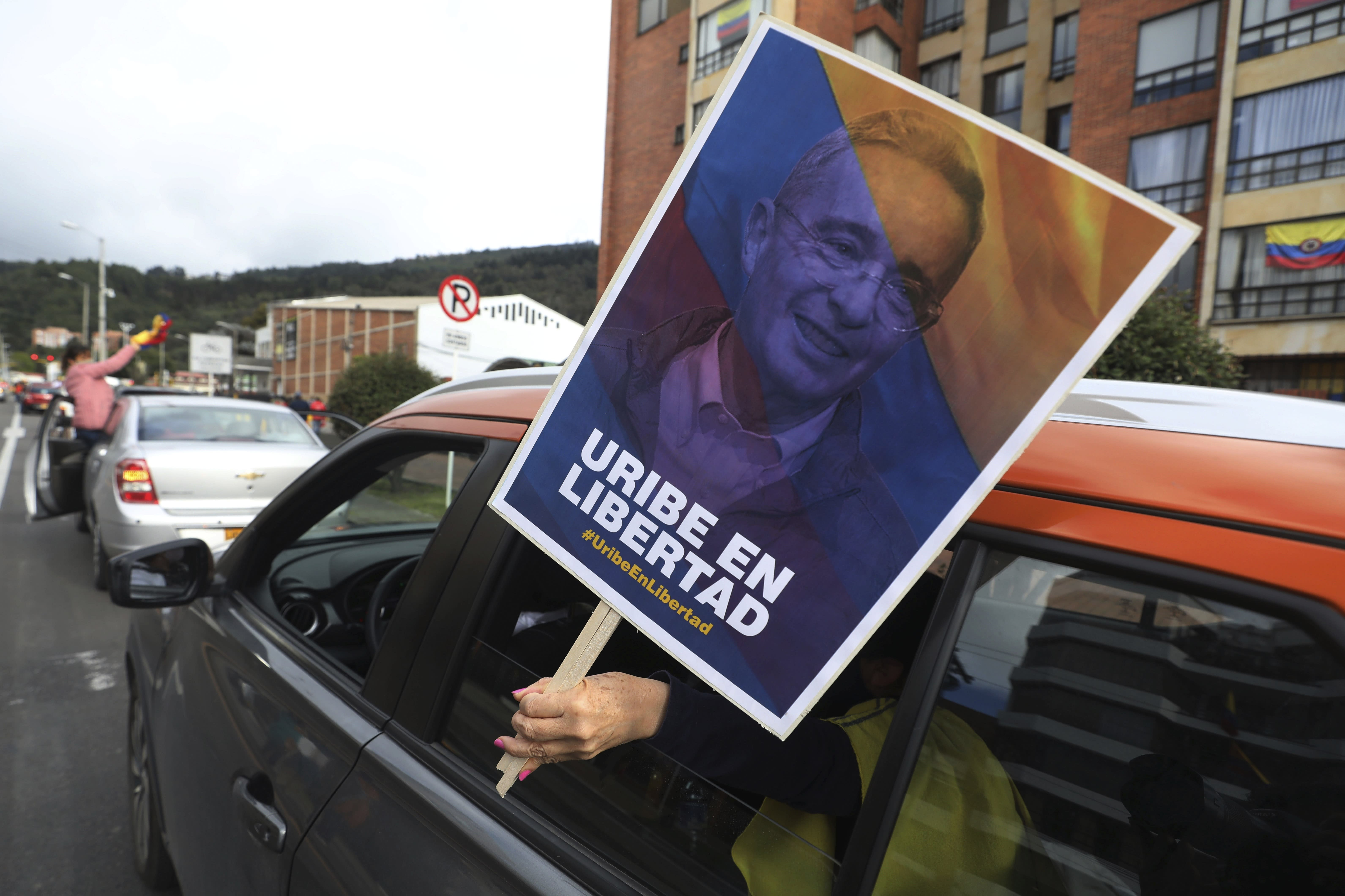 """A supporter of former President Alvaro Uribe holding a banner with an image of him with a message that reads in Spanish: """"Free Uribe"""", takes part in caravan to protest the Supreme Court decision to place Uribe under house arrest while it advances a witness tampering investigation against him, in Bogota, Colombia, Friday, Aug. 7, 2020. (AP Photo/Fernando Vergara)"""