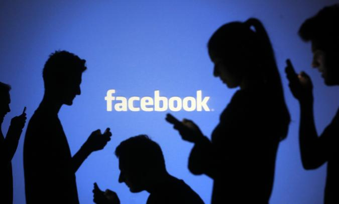 People are silhouetted as they pose with mobile devices in front of a screen projected with a Facebook logo, in this picture illustration taken in Zenica October 29, 2014. Facebook Inc warned on Tuesday of a dramatic increase in spending in 2015 and projected a slowdown in revenue growth this quarter, slicing a tenth off its market value. Facebook shares fell 7.7 percent in premarket trading the day after the social network announced an increase in spending in 2015 and projected a slowdown in revenue growth this quarter.   REUTERS/Dado Ruvic (BOSNIA AND HERZEGOVINA  - Tags: BUSINESS SCIENCE TECHNOLOGY BUSINESS LOGO)