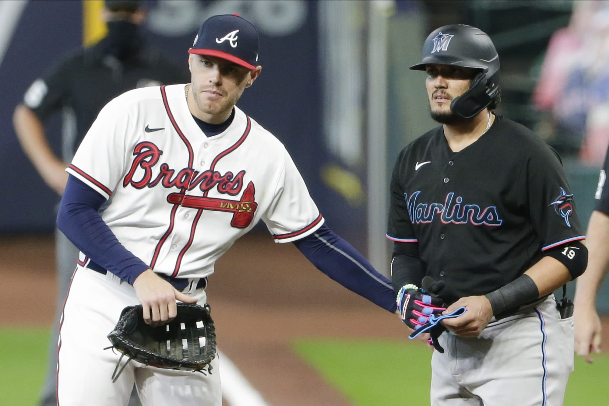 Atlanta Braves first baseman Freddie Freeman, left, taps Miami Marlins' Miguel Rojas, right, on the hip after Rojas was hit by a pitch during the eighth inning in Game 1 of a baseball National League Division Series Tuesday, Oct. 6, 2020, in Houston. The Braves won 9-5. (AP Photo/Michael Wyke)
