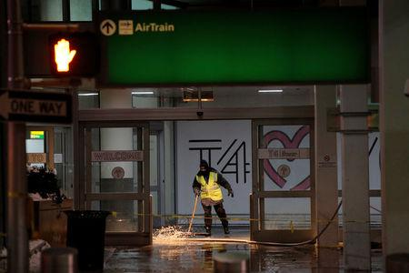 A worker attempts to remove water following a water main break in the arrivals area of Terminal 4 at John F. Kennedy International Airport in New York City, U.S. January 7, 2018. REUTERS/Andrew Kelly