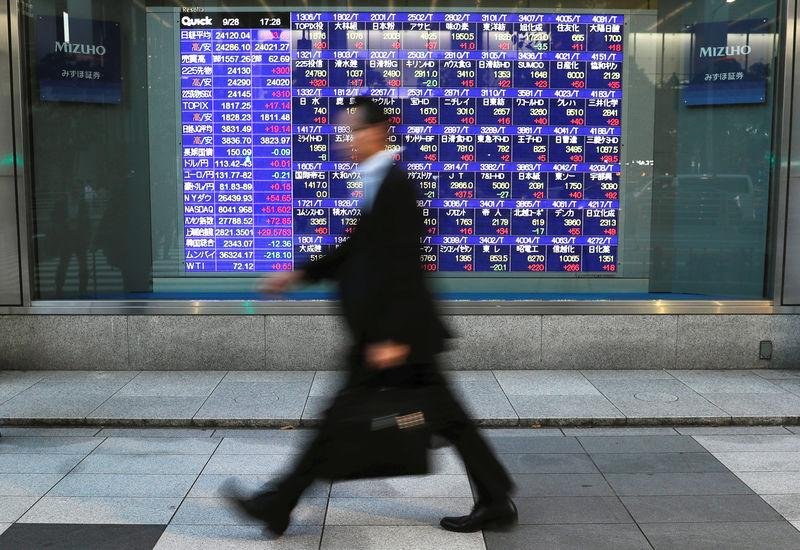 Passersby walk past in front of an electronic stock quotation board outside a brokerage in Tokyo