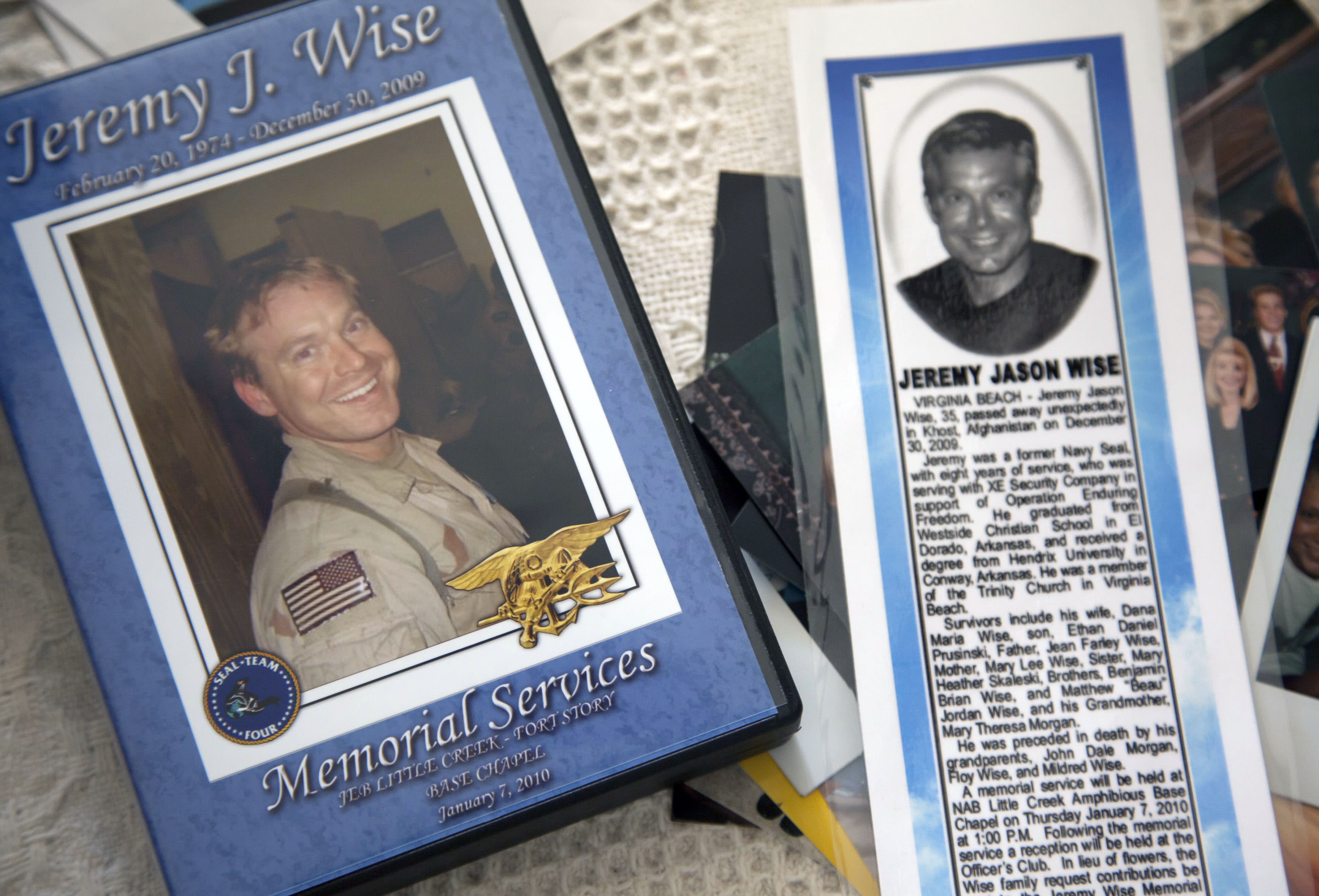 In this photo taken Jan. 24, 2012, the image of former Navy Seal Jeremy Wise is shown on the cover of a video of his 2009 memorial service and a newspaper obit displayed at his sister's home in Prescott, Ark. (AP Photo/Danny Johnston)