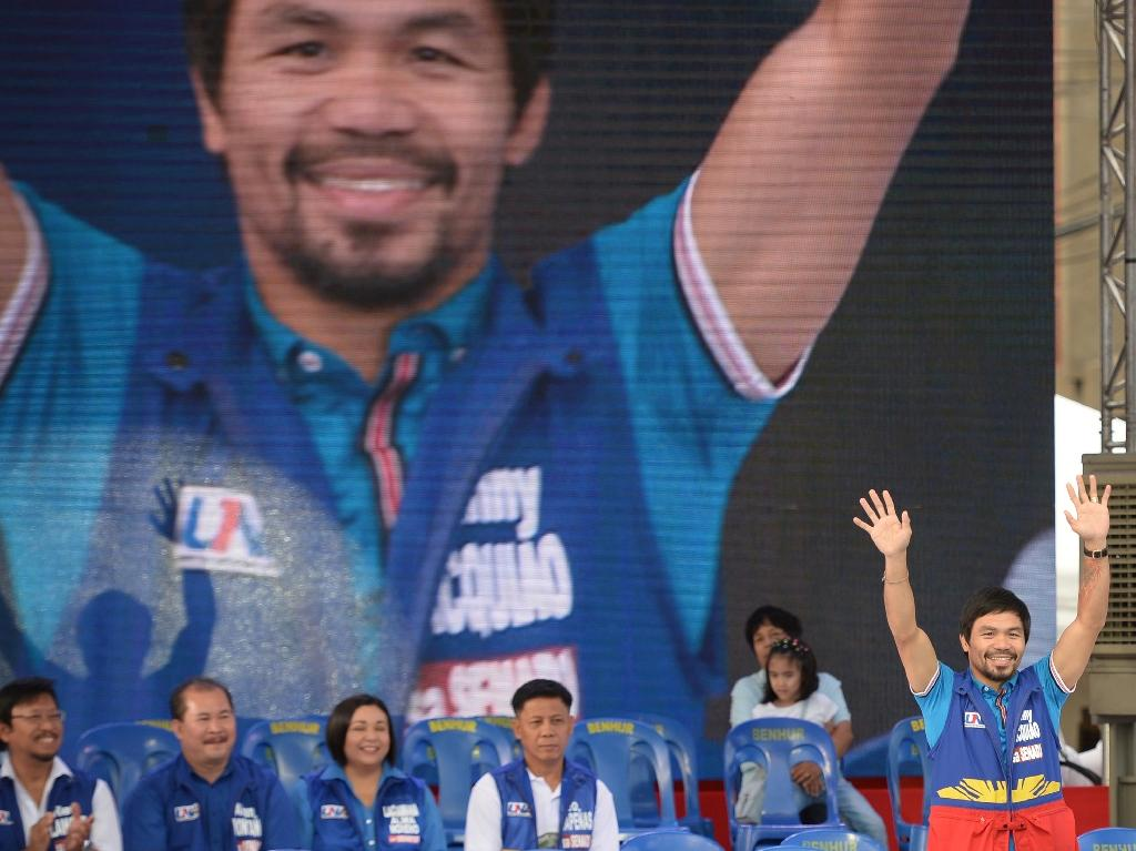 Senatorial candidate of the opposition party and boxing icon Manny Pacquiao greets supporters at a rally in Manila on February 9, 2016 (AFP Photo/Ted Aljibe)