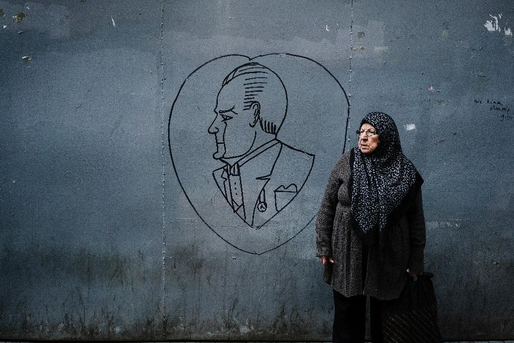 An elderly woman stands next to graffiti showing the founder of the Turkish Republic, Mustafa Kemal Ataturk, in Istanbul on October 28, 2015 (AFP Photo/Dimitar Dilkoff)