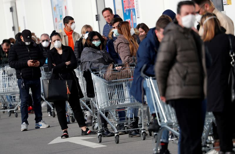 FILE PHOTO: People queue at a supermarket outside the town of Casalpusterlengo