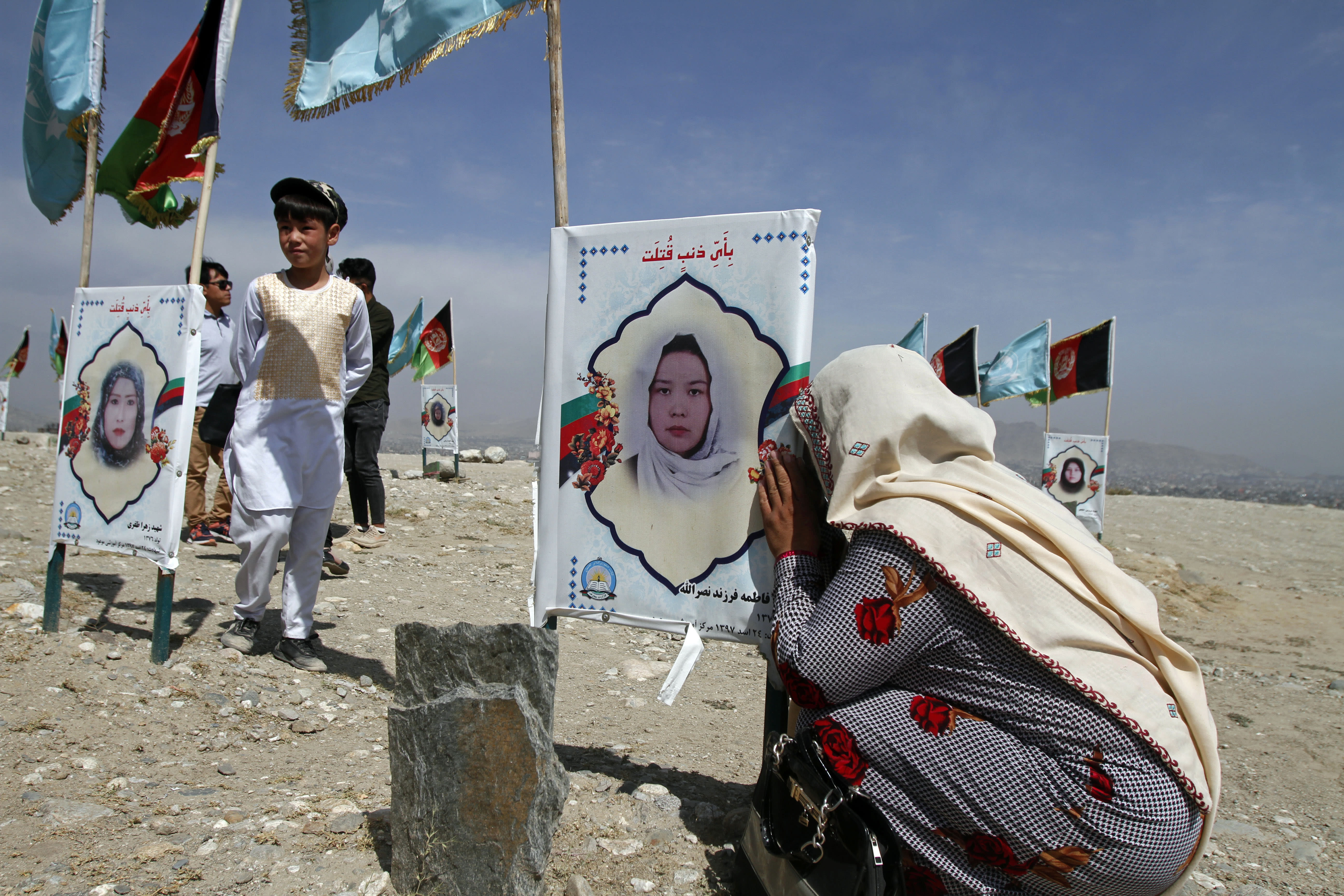 An Afghan woman cries next to the grave of her daughter, adorned with her picture, on the outskirts of Kabul, Afghanistan, Monday, Sept 14, 2020. Scores of friends and families of students who were killed in local conflicts are gathering in a cemetery to call for a permanent countrywide ceasefire from the parties to the intra-Afghan peace conference taking place in Doha, Qatar. (AP Photo/Rahmat Gul)