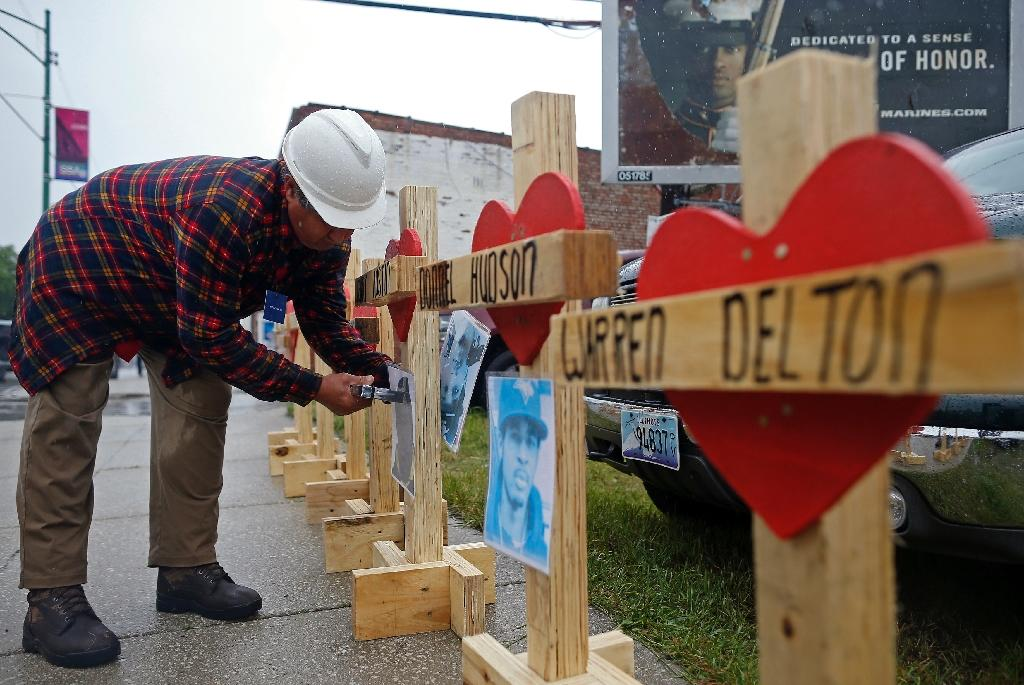 Greg Zanis staples a photograph to a wooden cross ahead of a prayer vigil and rally against violence in Chicago (AFP Photo/JIM YOUNG)