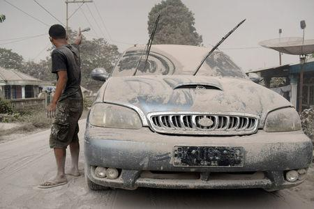 Ash from Mount Sinabung volcano covers a car and street following an eruption in Karo, North Sumatra, Indonesia February 19, 2018 in this photo taken by Antara Foto. Antara Foto/ Surianto Sembiring / via REUTERS