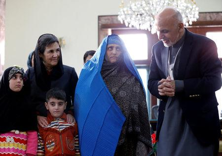 "Afghanistan's President Ashraf Ghani speaks to Sharbat Gula, the green-eyed ""Afghan Girl"" whose 1985 photo in National Geographic became a symbol of her country's wars, after she arrived in Kabul, Afghanistan November 9, 2016. REUTERS/Mohammad Ismail"