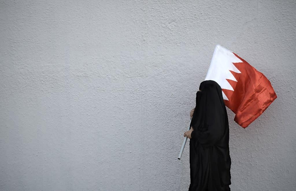 A woman holds the flag of Bahrain, a Shiite-majority Gulf kingdom