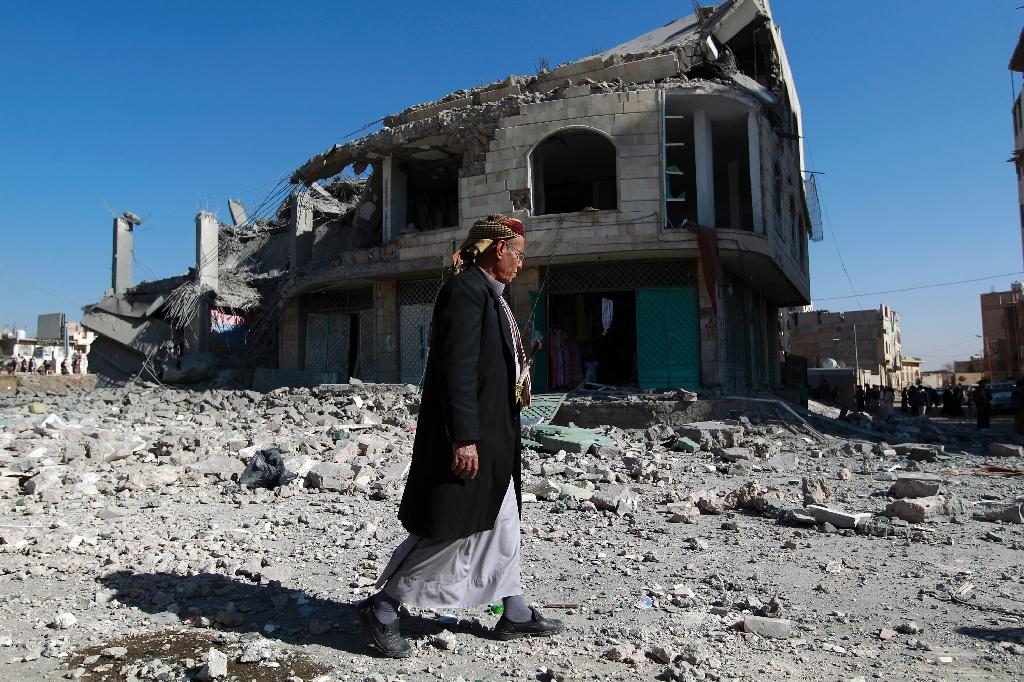 A Yemeni man walks past the site of a Saudi-led airstrike that targeted a building in the capital Sanaa in January 2016