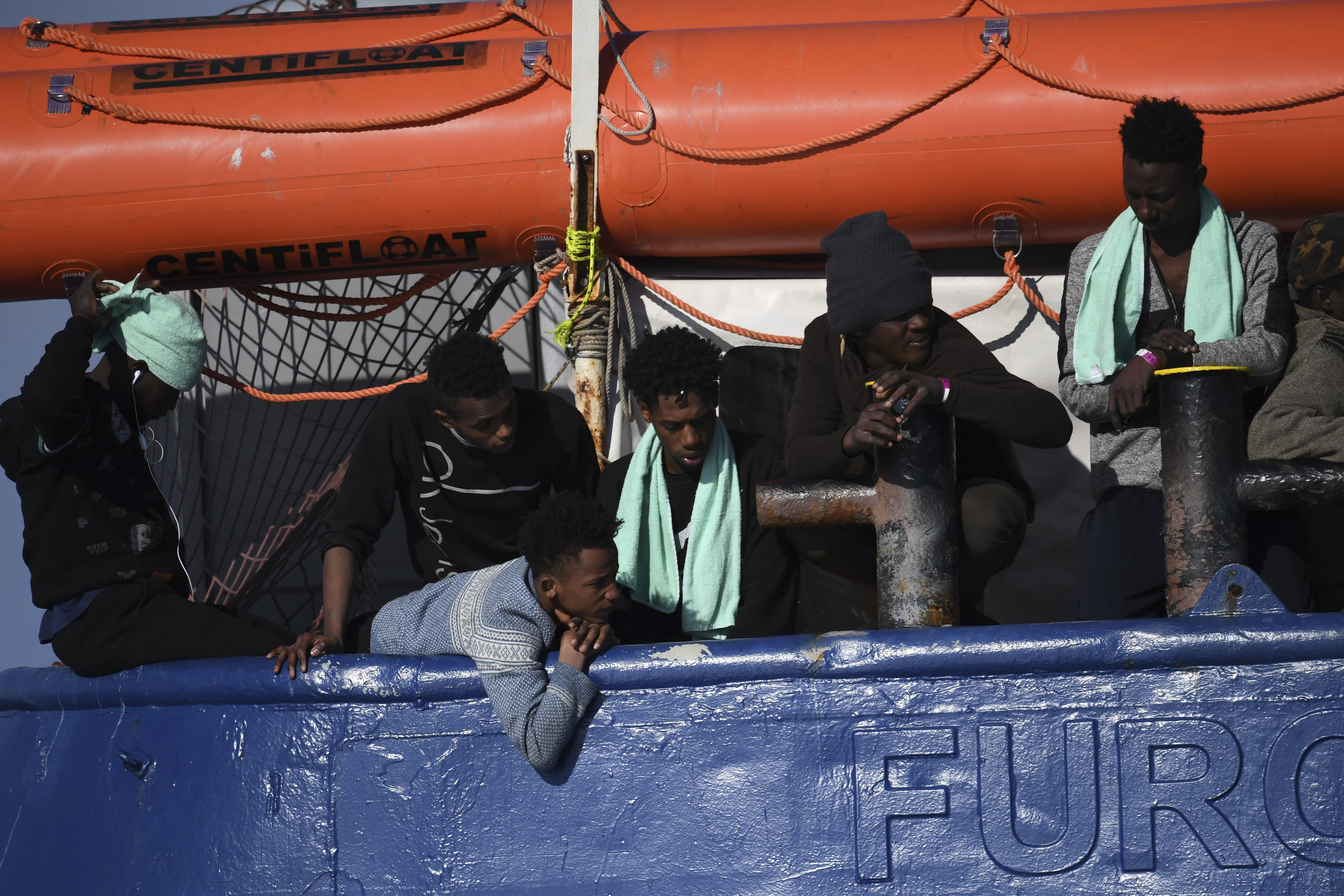 Migrants wait aboard the German humanitarian group's rescue boat Sea Watch 3, off the coast of Syracuse, Italy, Sunday, Jan. 27, 2019. The Italian coast guard is bringing socks, shoes, bread and fruit to 47 migrants who have been stranded at sea for nine days aboard a German ship. (AP Photo/Salvatore Cavalli)