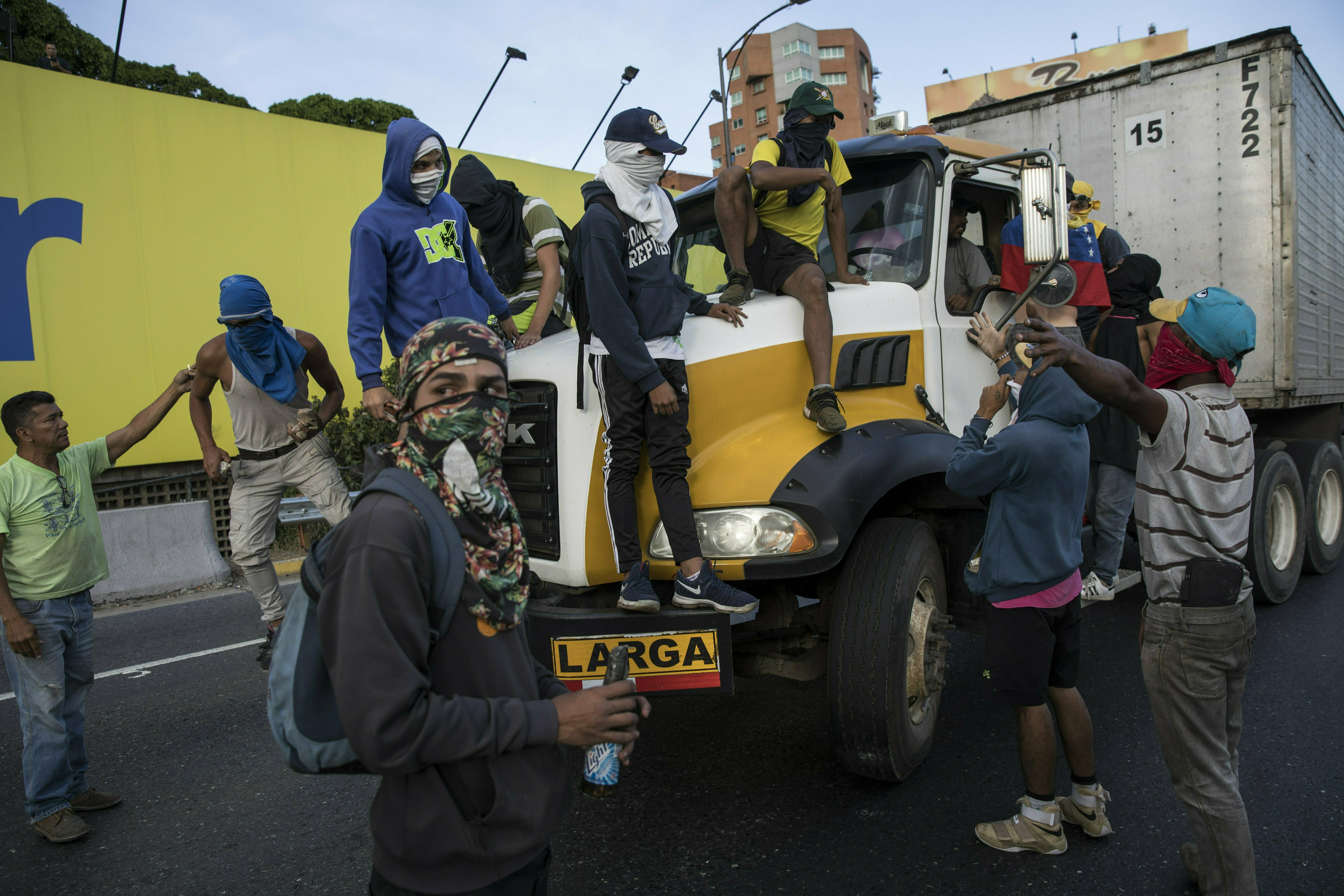 Anti-government protesters stop a truck while blocking a highway with a small group of demonstrators who were returning from a peaceful demonstration called by self-declared interim president Juan Guaido to demand the resignation of President Nicolas Maduro, in Caracas, Venezuela, Saturday, Feb. 2, 2019. (AP Photo/Rodrigo Abd)