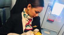 Stewardess stillt Baby einer Passagierin
