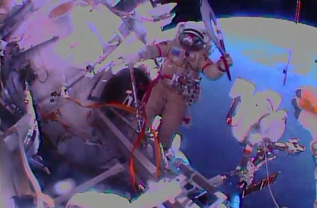 Russian cosmonauts take the Olympic torch for its first spacewalk ahead of Sochi games