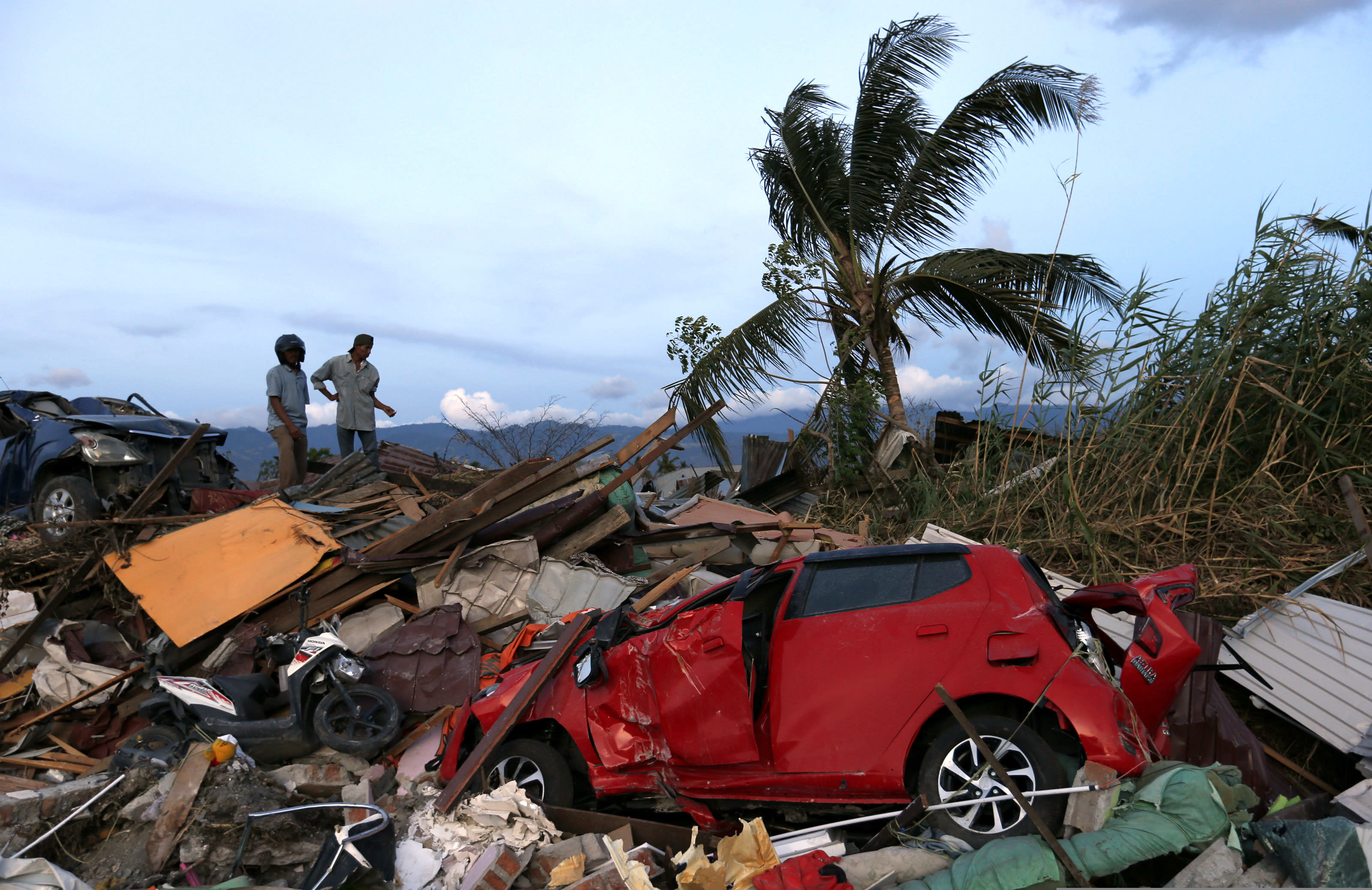 In this Oct. 7, 2018, file photo, men chat on top of the rubble at Petobo neighborhood, which was wiped out by the earthquake-triggered tsunami, in Palu, Central Sulawesi, Indonesia,. (AP Photo/Dita Alangkara, File)