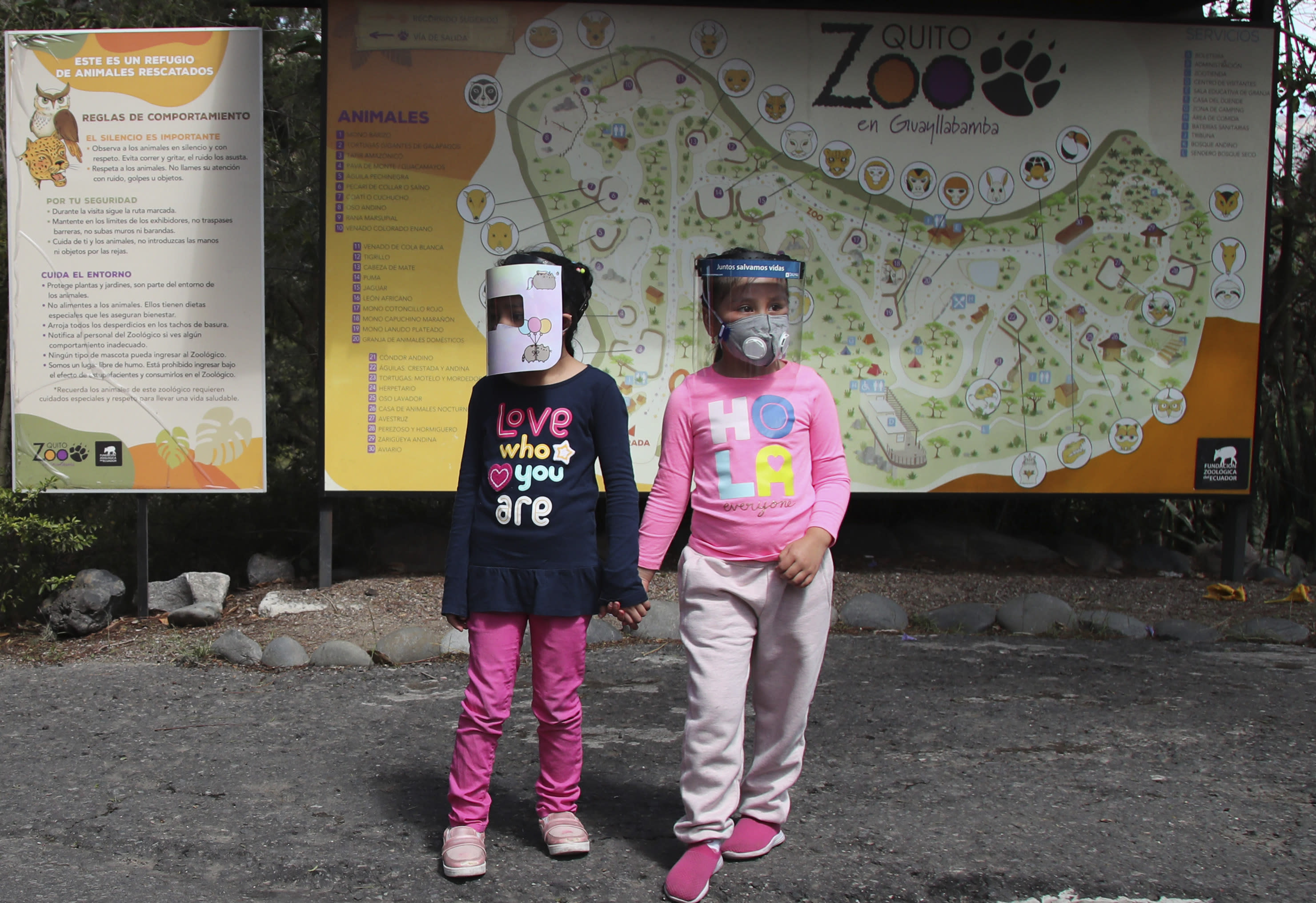Girls wearing face shields as a preventive measure against the new coronavirus wait for their parents to enter the zoo on the outskirts of Quito, in Guayllabamba, Ecuador, Wednesday, July 8, 2020. The zoo is reopening but with strict new social distancing protocols for visitors due to the COVID-19 pandemic. (AP Photo/Dolores Ochoa)