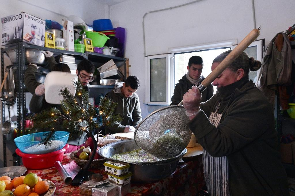 Carolynn Rockafellow (R) and volunteers help chef Talal Rankoussi to cook a meal at the 'Cafe Rits' in Ritsona refugee camp, some 80 km north of Athens (AFP Photo/Louisa GOULIAMAKI)