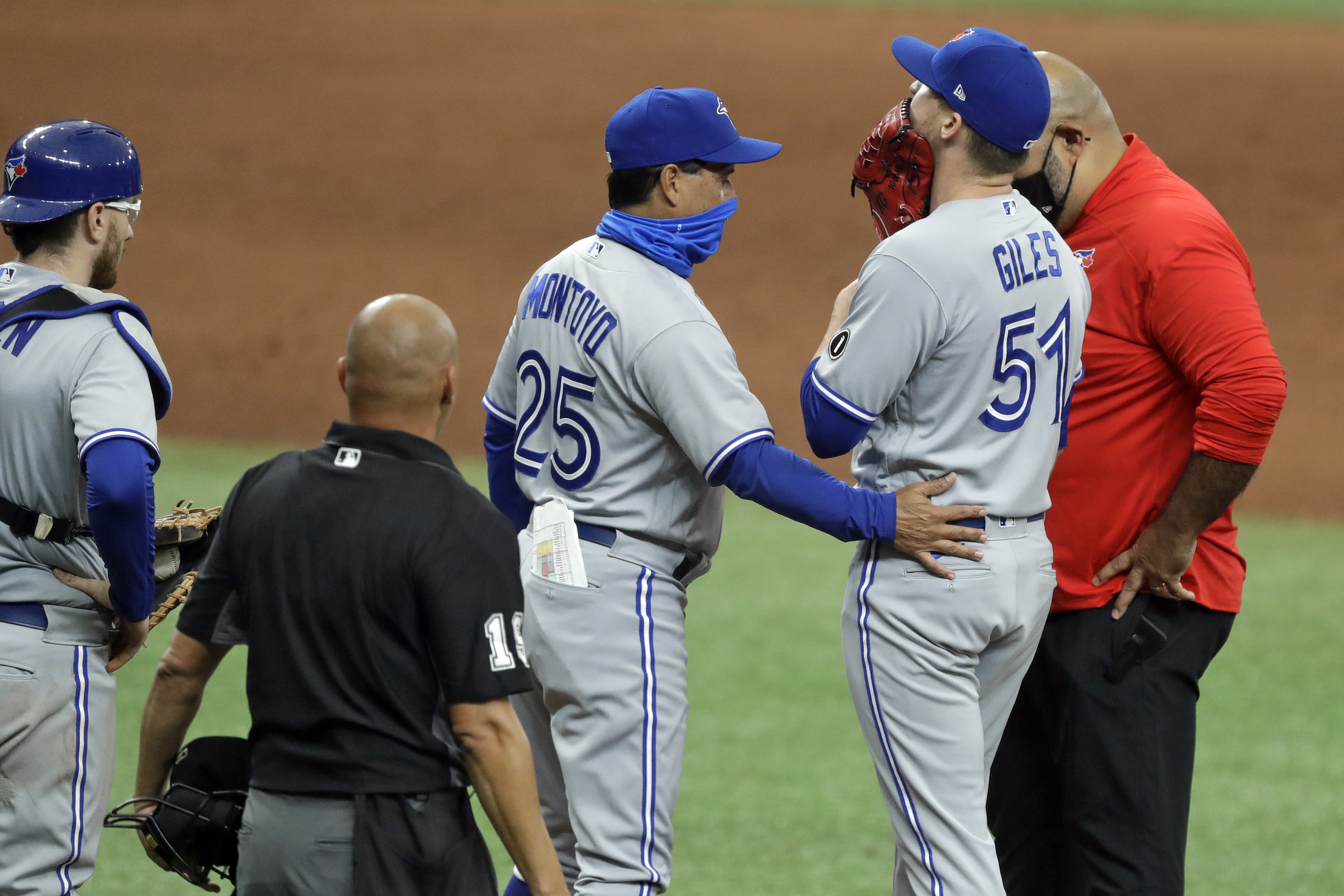 Toronto Blue Jays manager Charlie Montoya (25) checks on relief pitcher Ken Giles (51) after Giles hurt himself during the ninth inning of a baseball game against the Tampa Bay Rays Sunday, July 26, 2020, in St. Petersburg, Fla. Giles left the game. (AP Photo/Chris O'Meara)