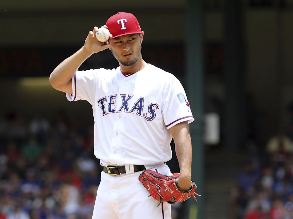 Texas Rangers starting pitcher Yu Darvish adjusts his cap as he works the first inning of a baseball game against the Los Angeles Angels in Arlington, Texas, Sunday, July 9, 2017.
