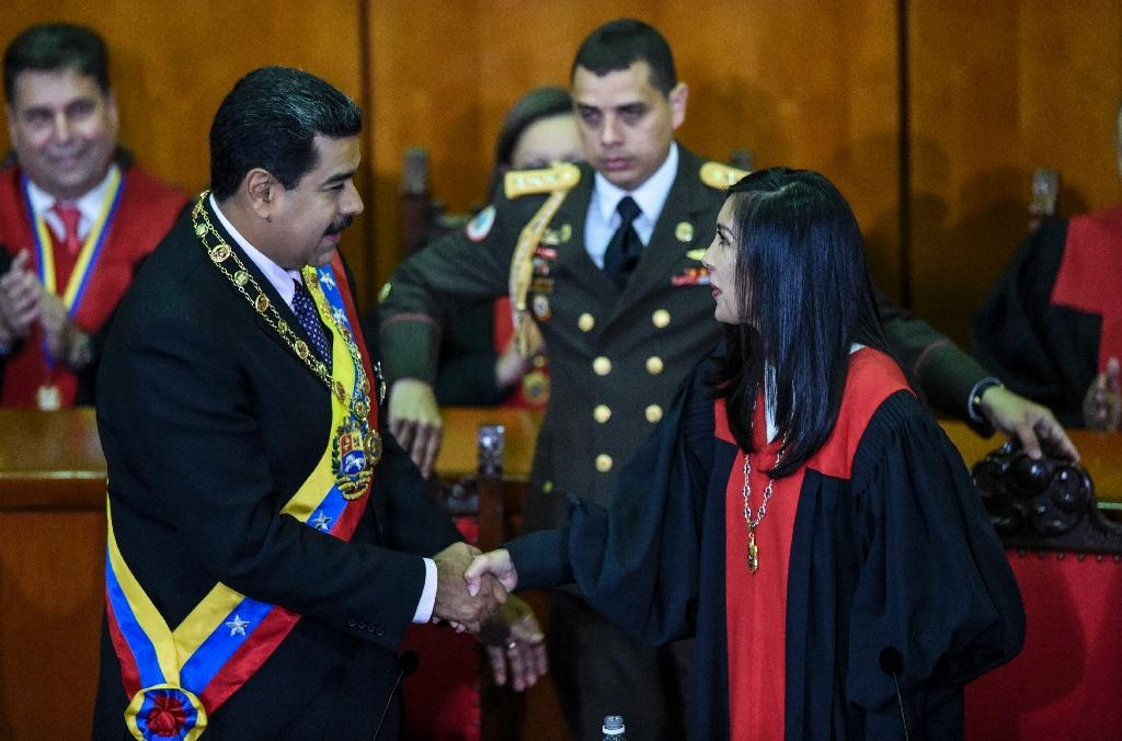 Venezuelan President Nicolas Maduro (L) shakes hands with President of Venezuela's Supreme Court of Justice Gladys Maria Gutierrez, after the ceremony where Maduro delivered a speech reviewing his year in office in Caracas on January 15, 2017 (AFP Photo/JUAN BARRETO)
