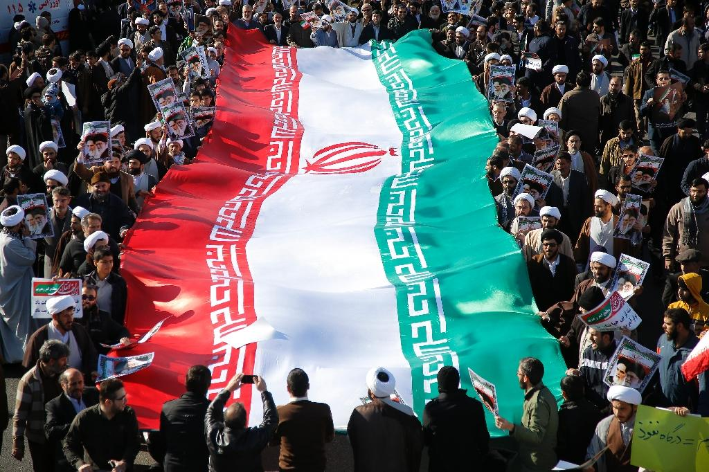 Pro-government demonstrators with a huge national flag march in Iran's holy city of Qom on January 3, 2018 (AFP Photo/Mohammad ALI MARIZAD)