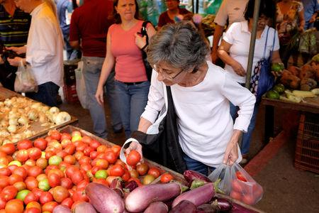 A woman selects tomatoes in a street market in Caracas, Venezuela August 18, 2018. REUTERS/Marco Bello