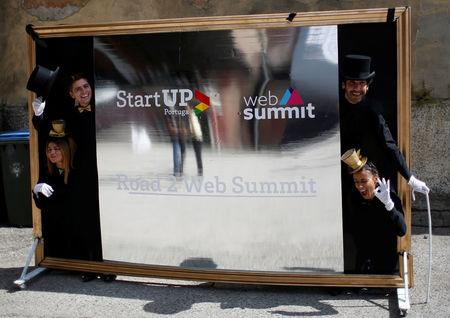 Entertainers stand behind a board announcing Europe's biggest tech conference, Web Summit, in Lisbon